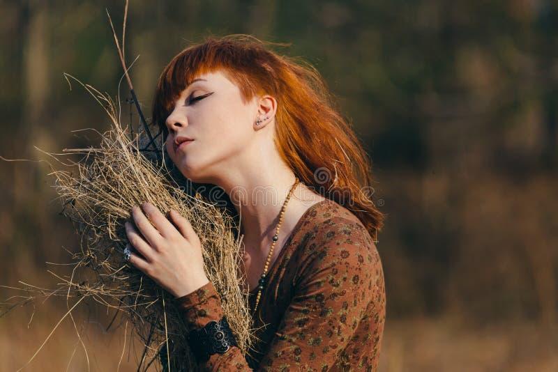Jovem mulher que anda no campo de grama secada dourado fotografia de stock