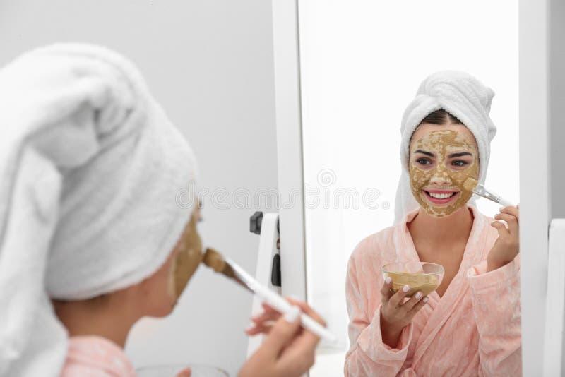 Jovem mulher que aplica a máscara da argila em sua cara perto do espelho fotos de stock royalty free