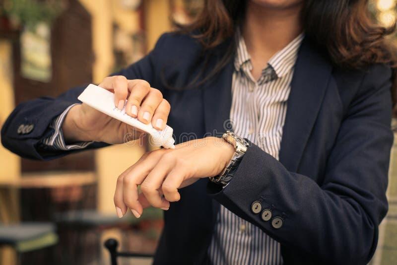 Jovem mulher que aplica a nata da mão Cuidado do corpo imagem de stock