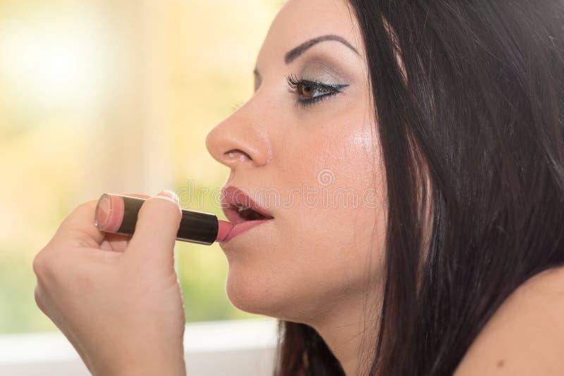 Jovem mulher que aplica o batom cor-de-rosa, efeito da luz foto de stock