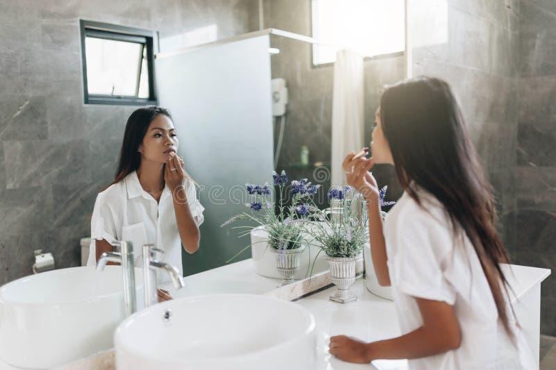 Jovem mulher que aplica o batom que olha o espelho fotos de stock royalty free