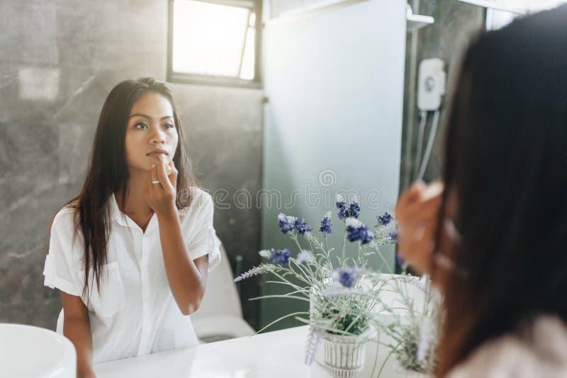 Jovem mulher que aplica o batom que olha o espelho imagem de stock