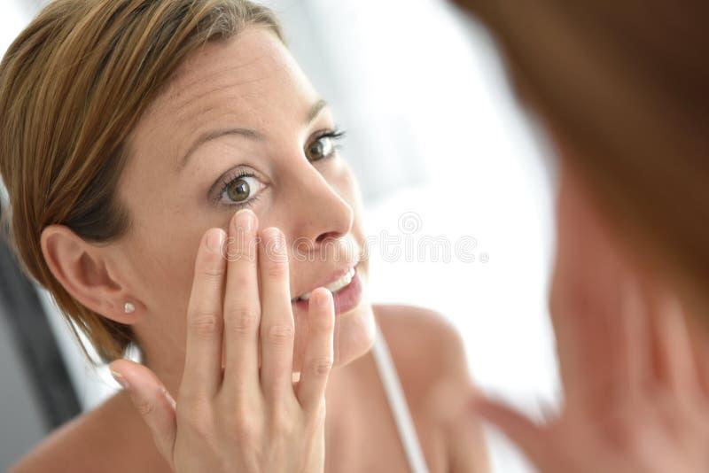 Jovem mulher que aplica o creme facial na manhã foto de stock