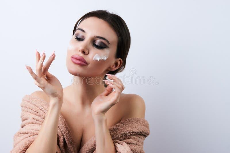Jovem mulher que aplica o creme hidratante em sua cara, close-up fotografia de stock