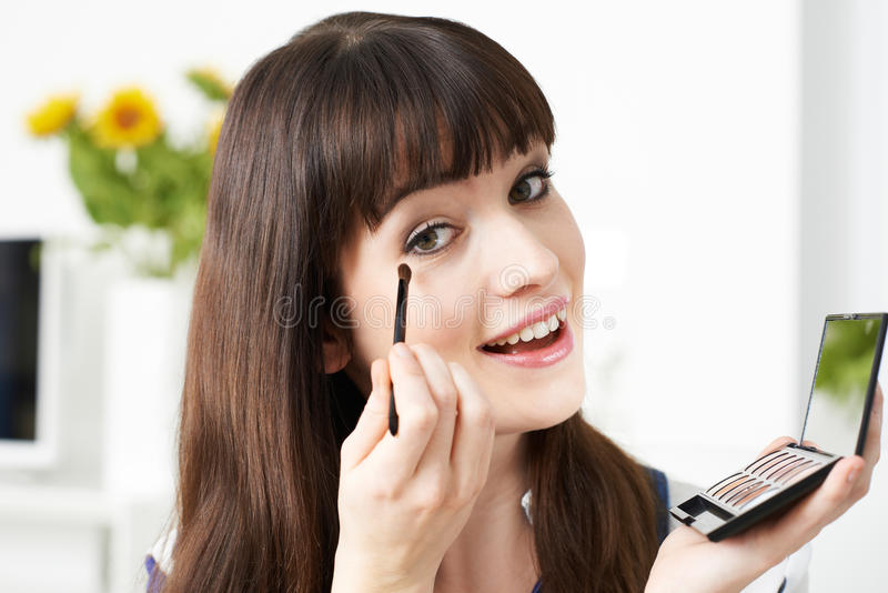 A jovem mulher que aplica o olho compõe em casa foto de stock