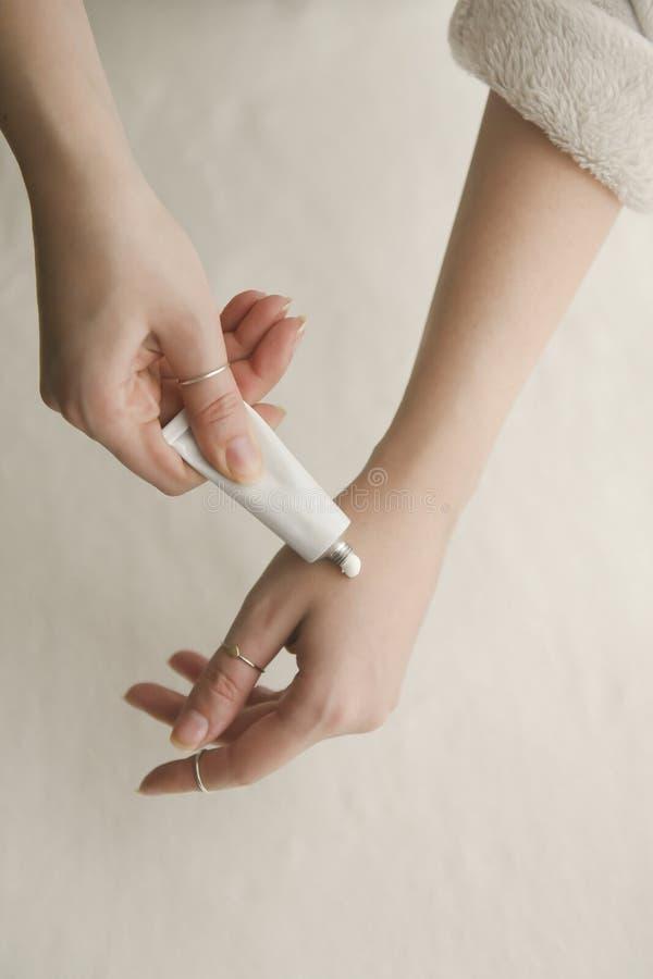 Jovem mulher que aplica um creme branco para cuidados com a pele fotos de stock royalty free