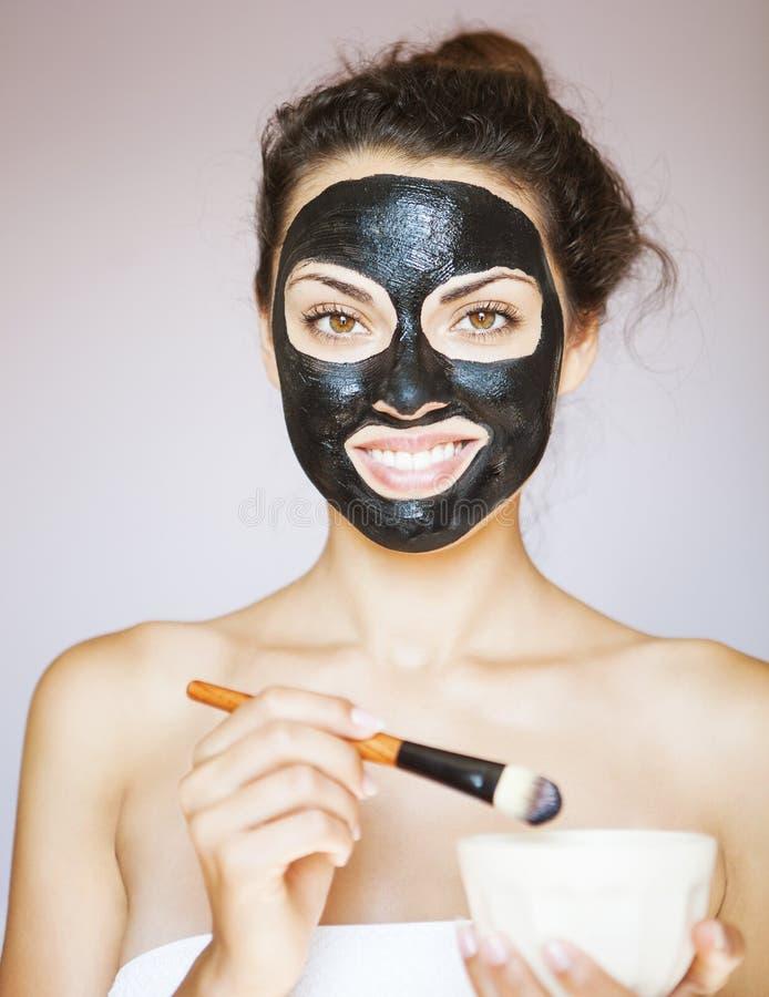 Jovem mulher que aplica uma máscara para a cara do blac terapêutico imagens de stock royalty free