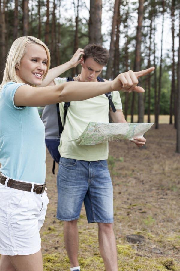 Jovem mulher que aponta afastado com o homem confuso que guarda o mapa na floresta fotografia de stock