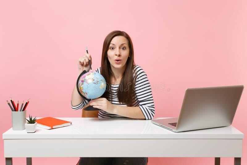Jovem mulher que aponta no globo com lápis, quando planejando das férias para sentar-se e trabalhar na mesa branca com PC contemp imagem de stock royalty free