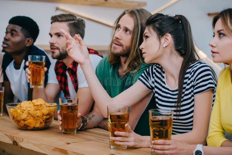 jovem mulher que aponta pelo dedo ao amigo e que guarda o vidro de cerveja quando outros amigos que olham o fósforo de futebol fotografia de stock