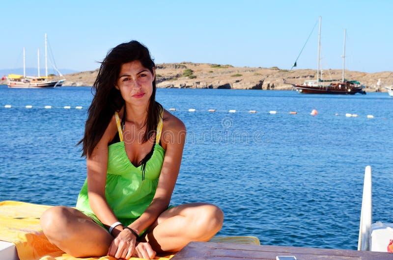 Jovem mulher que aprecia as férias de verão que sentam no oon sunbed a praia imagens de stock royalty free