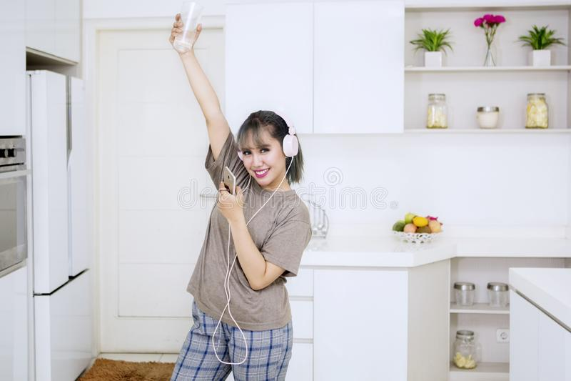 Jovem mulher que aprecia a música na cozinha imagem de stock