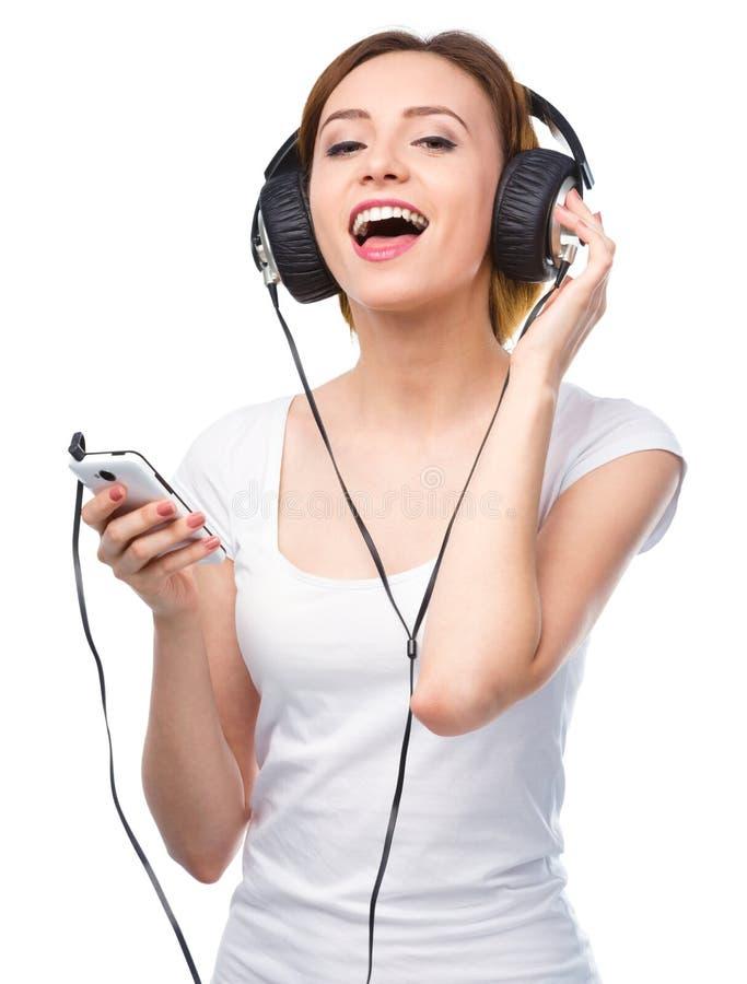Jovem mulher que aprecia a música usando fones de ouvido foto de stock royalty free