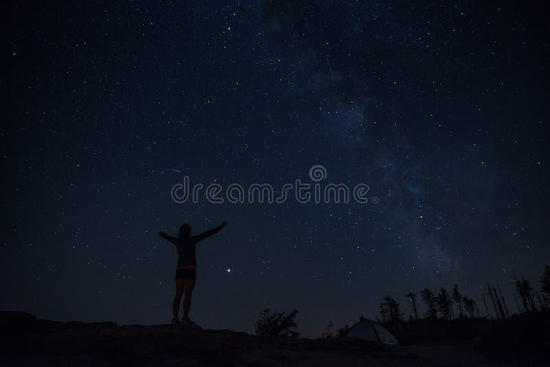 Jovem mulher que aprecia a noite estrelado na fuga de montanha foto de stock royalty free