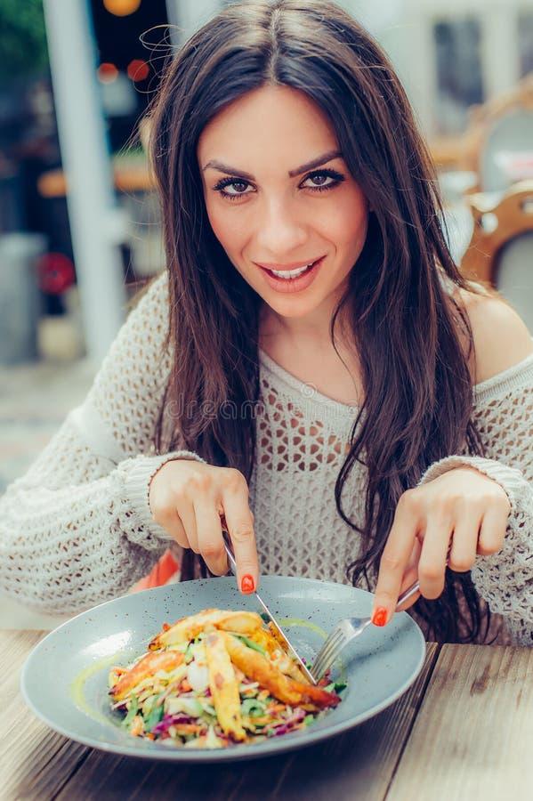 Jovem mulher que aprecia o alimento em um restaurante, tendo seu brea do almoço imagem de stock royalty free
