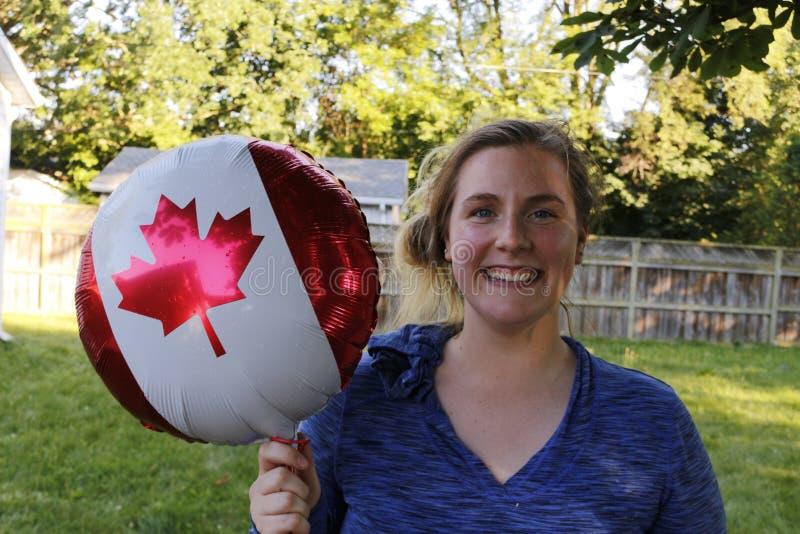 Jovem mulher que aprecia o feriado do dia de Canadá, guardando uma bandeira canadense imagem de stock royalty free