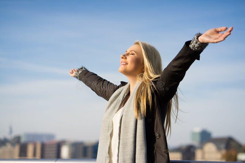 Jovem mulher que aprecia o sol do outono imagem de stock