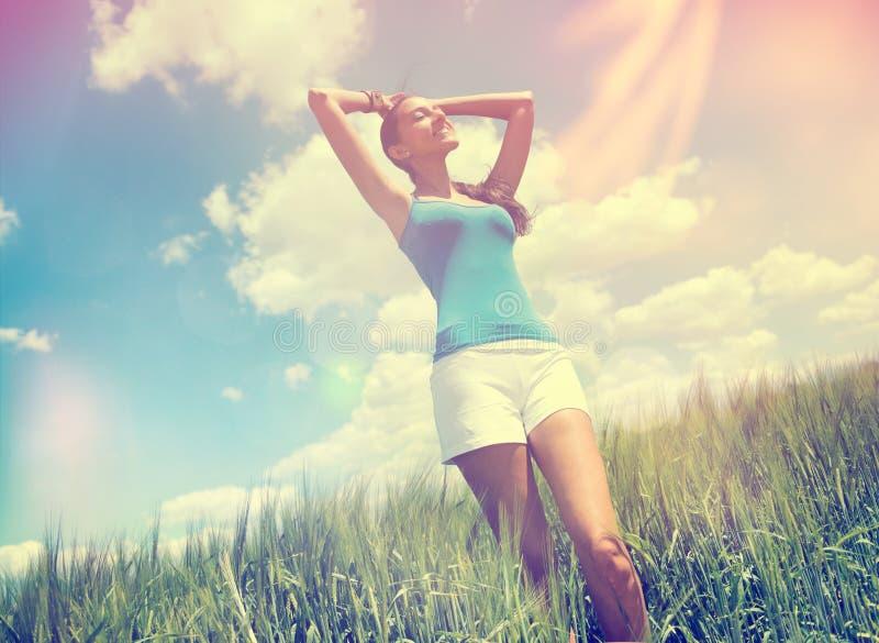 Jovem mulher que aprecia o sol morno do verão imagem de stock