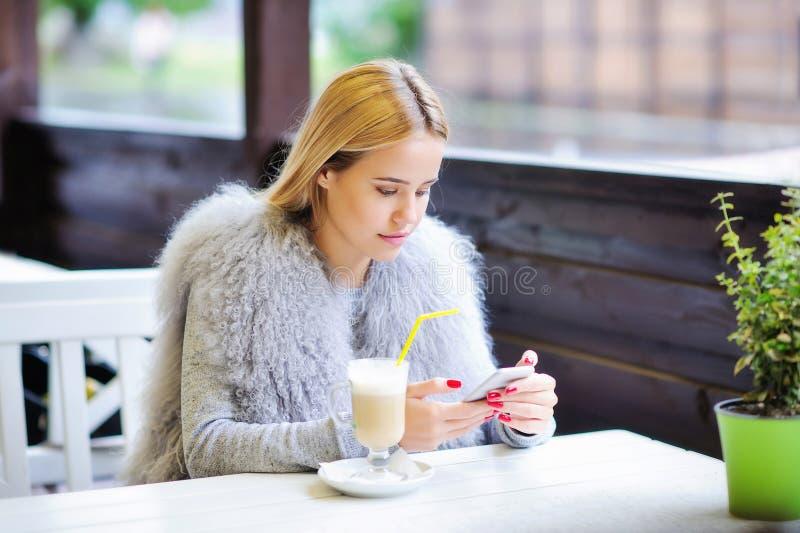 Jovem mulher que aprecia seu tempo durante a ruptura de café foto de stock royalty free