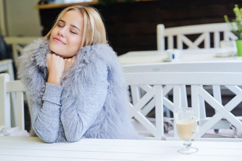 Jovem mulher que aprecia seu tempo durante a ruptura de café fotos de stock royalty free