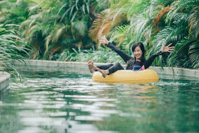 Jovem mulher que aprecia a tubulação na associação preguiçosa do rio foto de stock