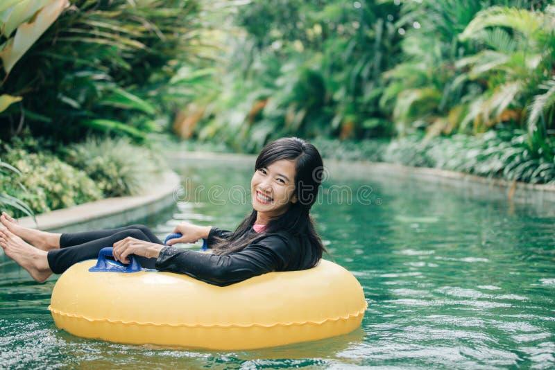 Jovem mulher que aprecia a tubulação na associação preguiçosa do rio fotografia de stock royalty free
