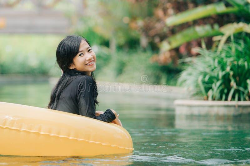 Jovem mulher que aprecia a tubulação na associação preguiçosa do rio fotos de stock