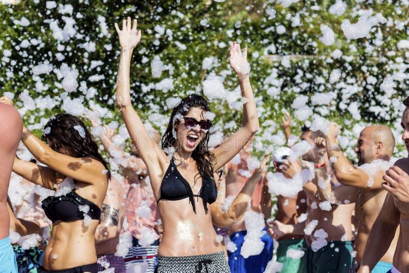 Jovem mulher que aprecia um partido da espuma na praia foto de stock royalty free