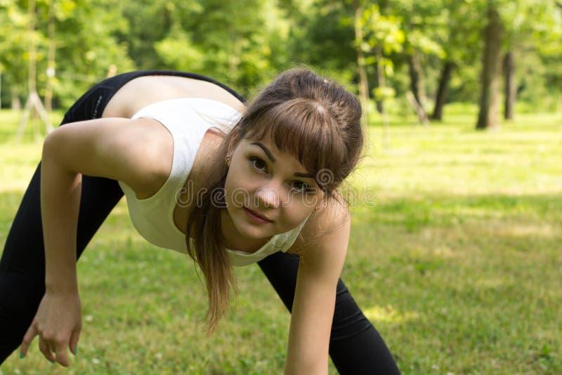 Jovem mulher que aquece-se no parque foto de stock royalty free