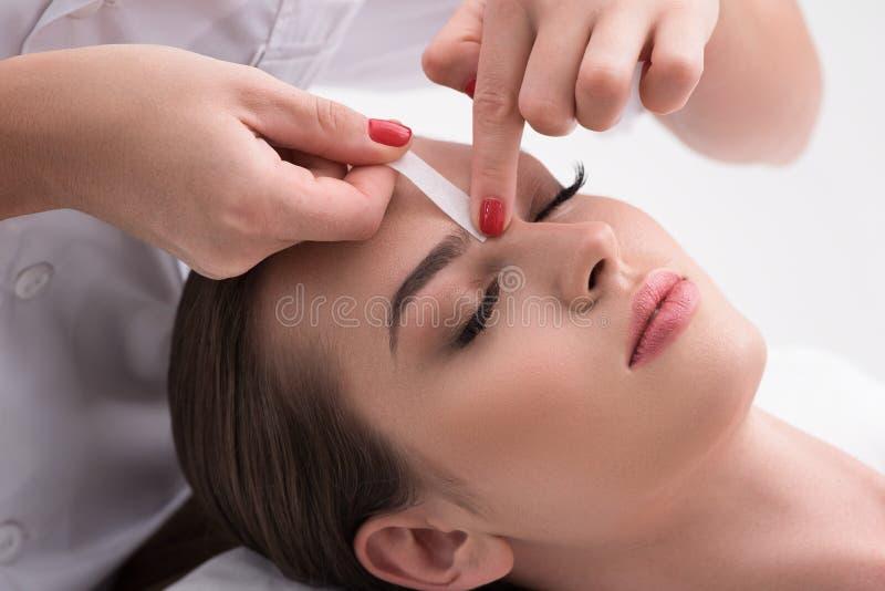 Jovem mulher que arranca suas sobrancelhas no bar da beleza foto de stock royalty free