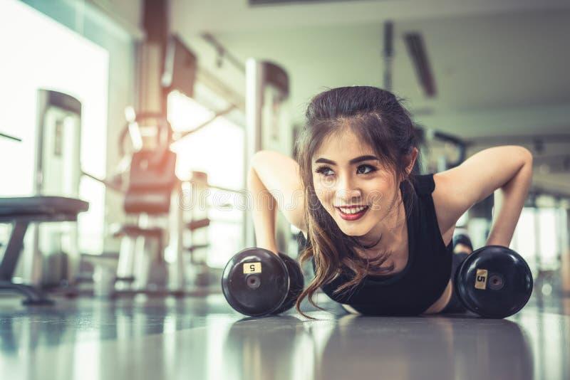 A jovem mulher que asiática fazer empurra levanta com peso no assoalho no fitne fotos de stock royalty free