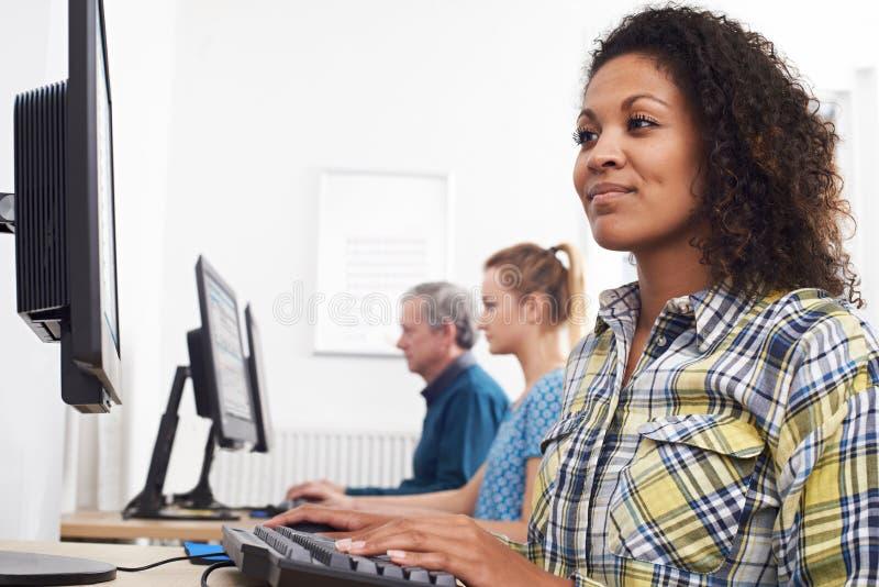 Jovem mulher que atende à classe do computador fotografia de stock