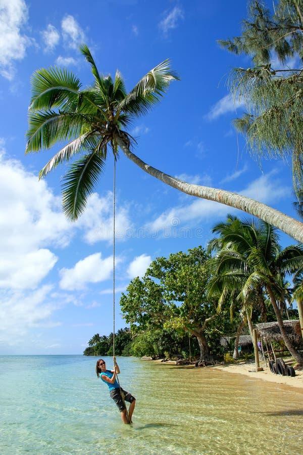 Jovem mulher que balança em um balanço da corda na ilha de Pangaimotu perto de T fotografia de stock royalty free