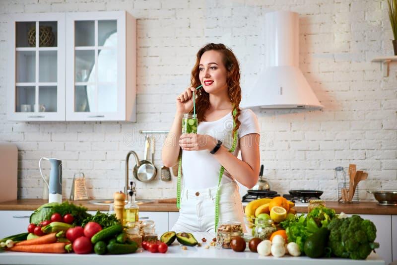 Jovem mulher que bebe a água fresca com pepino, limão e folhas da hortelã do vidro na cozinha Estilo de vida e comer saud?veis fotografia de stock royalty free