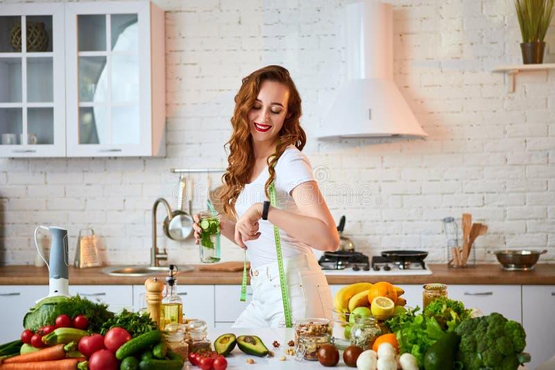 Jovem mulher que bebe a água fresca com pepino, limão e folhas da hortelã do vidro na cozinha Estilo de vida e comer saud?veis imagens de stock