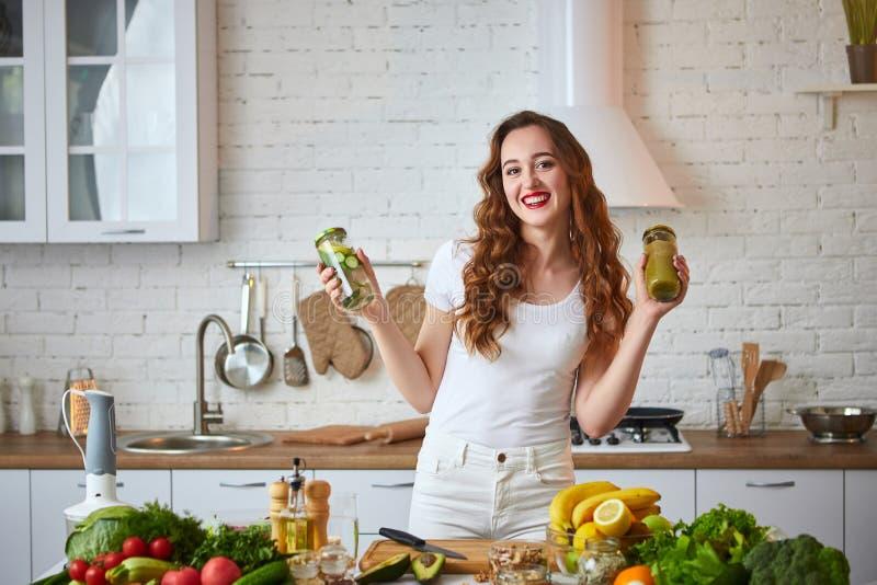 A jovem mulher que bebe o batido verde e a água fresca com pepino, limão, sae da hortelã na mesa de cozinha com os frutos e foto de stock