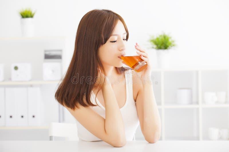 Jovem mulher que bebe o chá quente fotos de stock royalty free