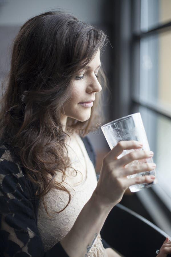 Jovem mulher que bebe um vidro da pinta da água de gelo fotos de stock royalty free