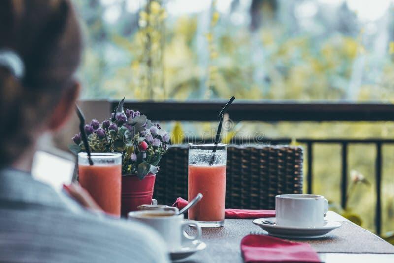 Jovem mulher que bebe uma xícara de café na manhã com a opinião da selva durante férias luxuosas na ilha de Bali imagem de stock