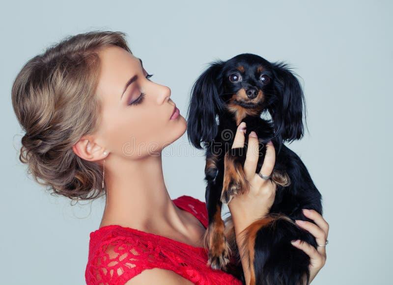 Jovem mulher que beija o cachorrinho no fundo branco fotografia de stock