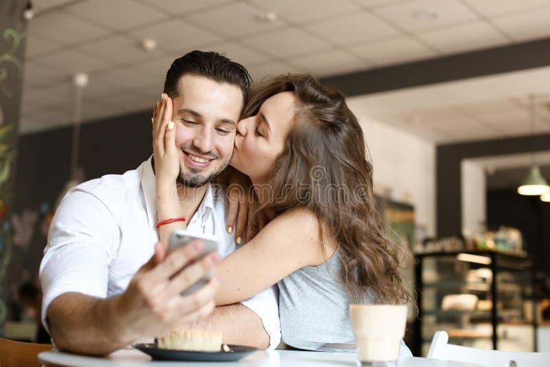 Jovem mulher que beija o homem que usa o smartphone no café e comendo o bolo fotografia de stock royalty free