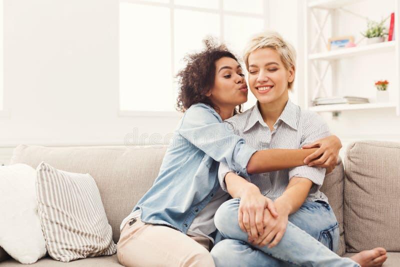 Jovem mulher que beija seu amigo no mordente fotografia de stock