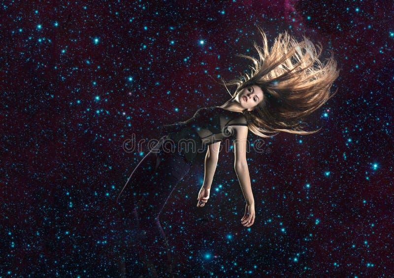 Jovem mulher que cai através do espaço foto de stock