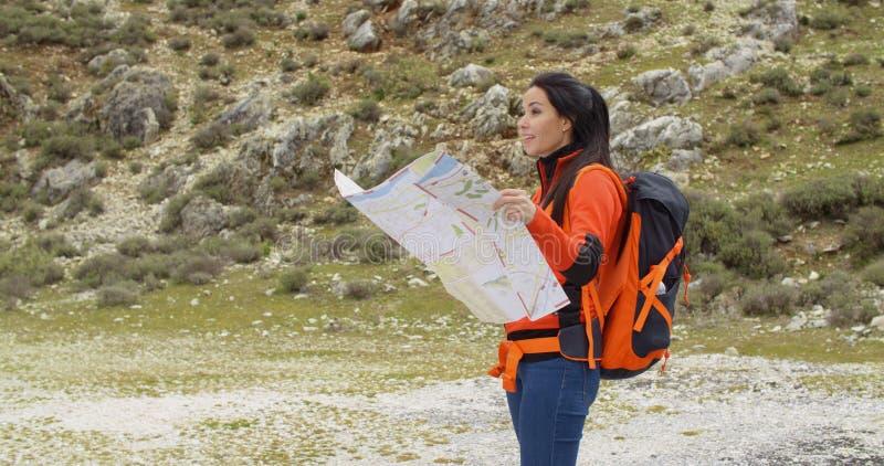 Jovem mulher que caminha para fora verificando um mapa fotografia de stock royalty free