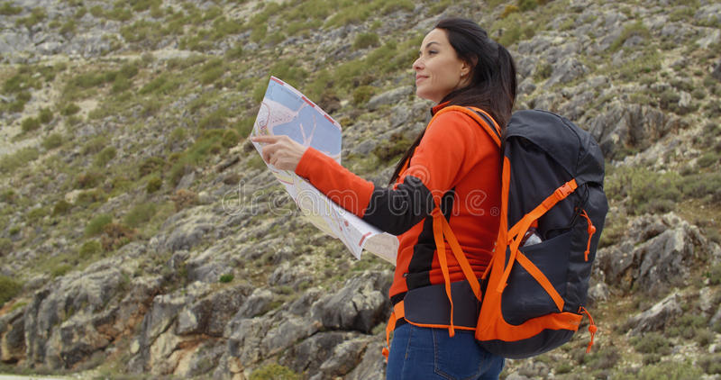 Jovem mulher que caminha para fora verificando um mapa imagens de stock