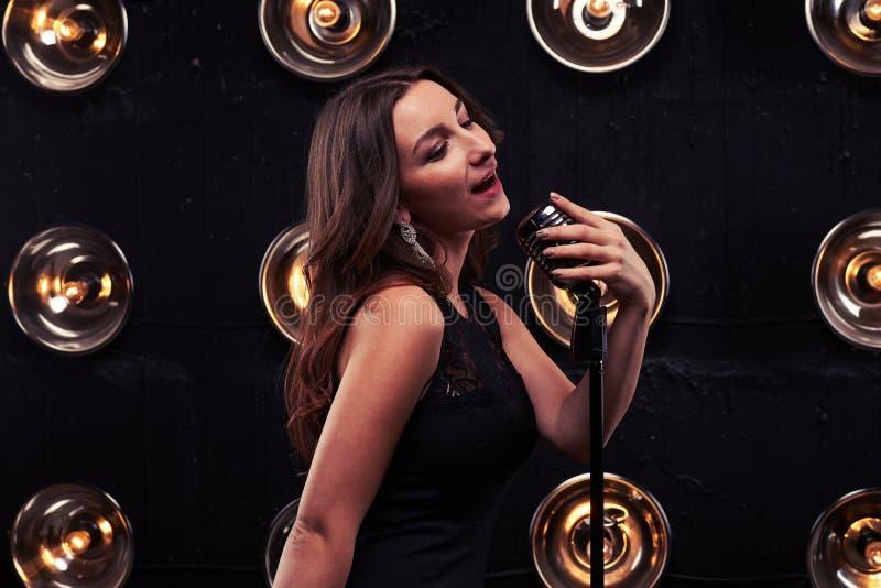 Jovem mulher que canta em um microph de prata retro do estúdio fotografia de stock