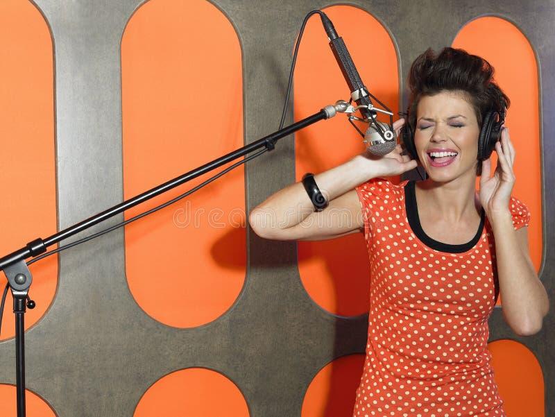 Jovem mulher que canta no estúdio imagens de stock