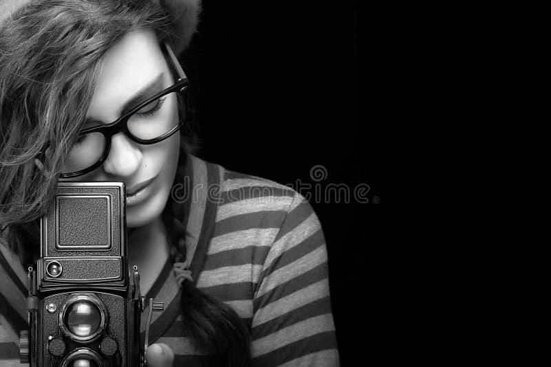 Jovem mulher que captura a foto usando a câmera do vintage Por monocromático fotografia de stock