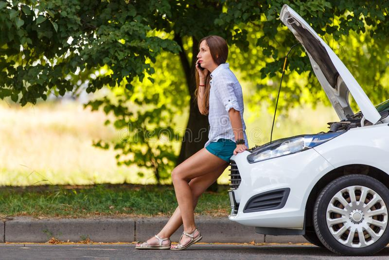 Jovem mulher que chama para a ajuda no carro quebrado imagens de stock