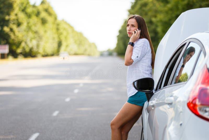 Jovem mulher que chama para a ajuda no carro quebrado imagem de stock